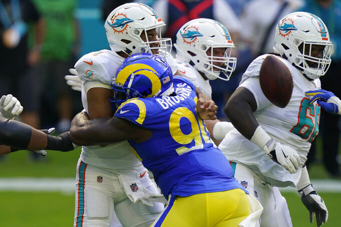 Los Angeles Rams defensive end Michael Brockers (90) hits Miami Dolphins quarterback Tua Tagovailoa (1) that causes Tagavailoa to fumble the ball, during the first half of an NFL football game, Sunday, Nov. 1, 2020, in Miami Gardens, Fla. (AP Photo/Lynne Sladky)