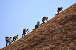 Tourists climb the sandstone monolith called Uluru that dominates Australia's arid center at Uluru-Kata Tjuta National Park, Friday, Oct. 25, 2019, the last day climbing is allowed. The end of visitors enjoying the panoramic views of the incongruously flat Outback surrounds from the rock's summit also marks indigenous Australians finding a new voice in national decision-making. (Lukas Coch/AAP Image via AP)
