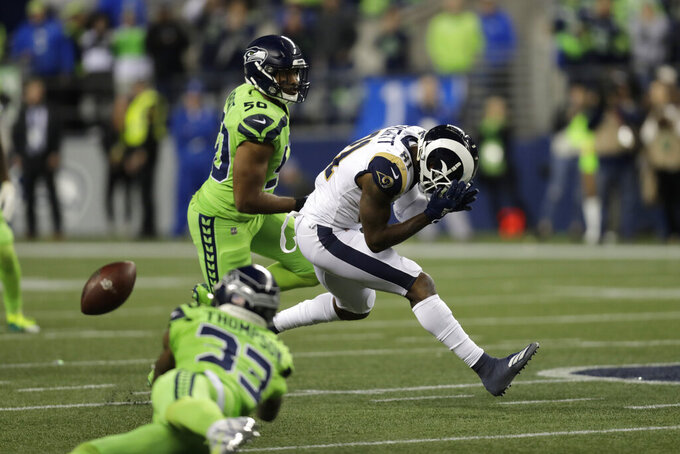 Los Angeles Rams tight end Gerald Everett, right, reacts after missing a pass that was intercepted by Seattle Seahawks free safety Tedric Thompson, front left, as as Seahawks' K.J. Wright, back left, watches during the second half of an NFL football game Thursday, Oct. 3, 2019, in Seattle. (AP Photo/Stephen Brashear)
