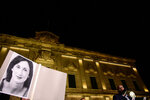 A protester holds up a picture of murdered reporter Daphne Caruana Galizia on the second day of a demonstration outside Malta's prime minister's office in Valletta, Malta, early Tuesday, Nov. 26, 2019. On Wednesday, Nov. 27, 2019 Maltese police arrested Prime Minister Joseph Muscat's former chief of staff Keith Schembri for questioning as a person of interest in the murder of the journalist. (AP Photo/Str)