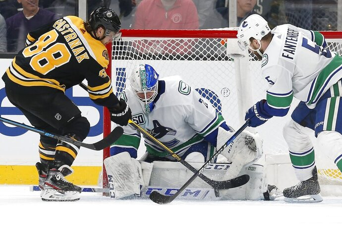Vancouver Canucks' Jacob Markstrom (25) blocks a shot by Boston Bruins' David Pastrnak (88) as Oscar Fantenberg (5) defends during the third period of an NHL hockey game in Boston, Tuesday, Feb. 4, 2020. (AP Photo/Michael Dwyer)