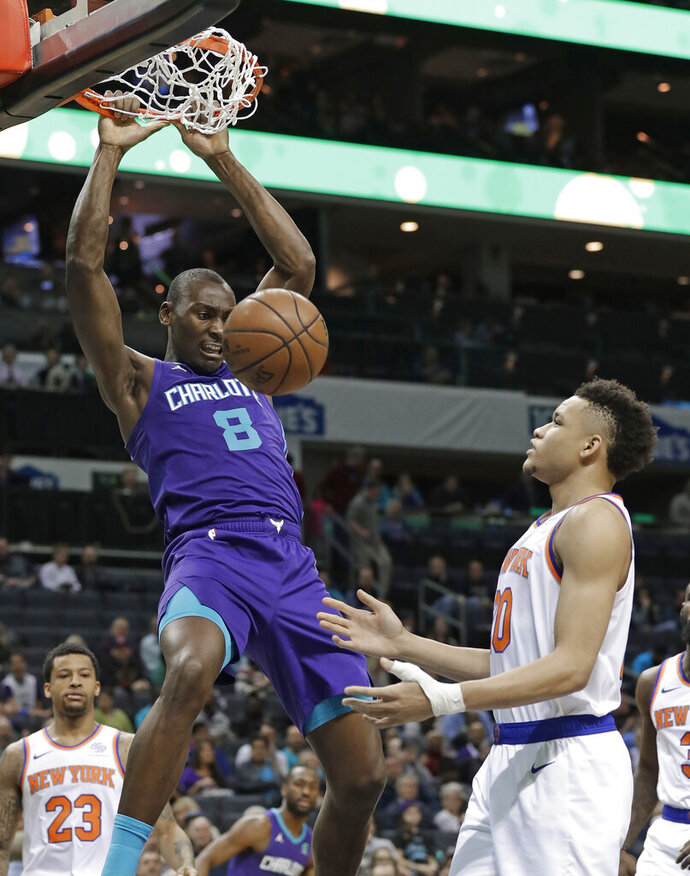 Charlotte Hornets' Bismack Biyombo (8) dunks against New York Knicks' Kevin Knox (20) during the first half of an NBA basketball game in Charlotte, N.C., Monday, Jan. 28, 2019. (AP Photo/Chuck Burton)