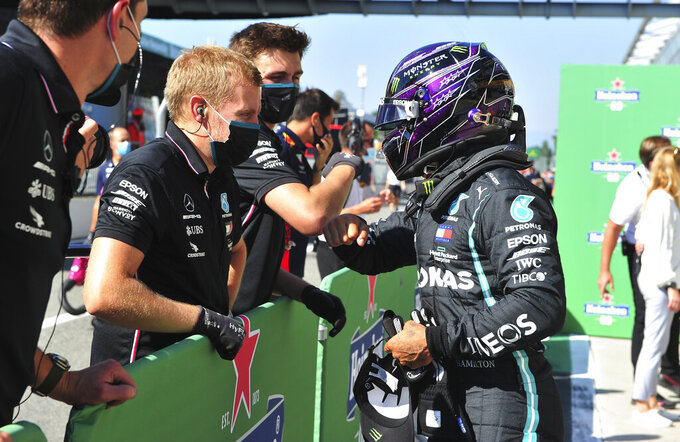 Mercedes driver Lewis Hamilton, right, of Britain celebrates after clocking the fastest time during the qualifying session for Sunday's Italian Formula One Grand Prix, at the Monza racetrack in Monza, Italy, Saturday, Sept. 5, 2020. (Jennifer Lorenzini/Pool via AP)