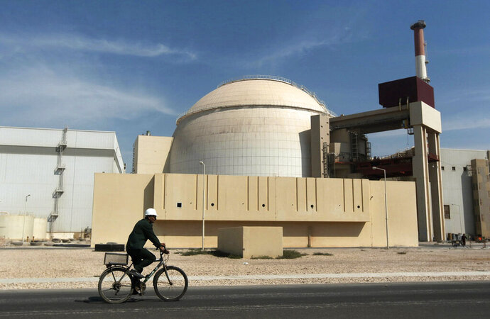 FILE - In this Oct. 26, 2010, file photo, a worker rides a bicycle in front of the reactor building of the Bushehr nuclear power plant, just outside the southern city of Bushehr. Iran said Friday, May 29, 2020, its experts would continue nuclear development activities, despite sanctions imposed earlier this week on their fellow scientists by the United States. (AP Photo/Mehr News Agency, Majid Asgaripour, File)