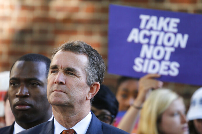 FILE - In this July 9, 2019 file photo, Virginia Gov. Ralph Northam, right, listens to speakers along with Richmond Mayor Levar Stoney, left, during a rally at the State Capitol in Richmond, Va. As the co-founder and CEO of MVM Inc., Dario Marquez Jr. oversaw hundreds of millions of dollars in federal contracts for work done everywhere from Iraq to Guantanamo Bay, Cuba.  Marquez has contributed nearly half a million dollars to Democratic politicians and causes in Virginia over the past decade.  A small but vocal group of activists are calling for Democrats to stop taking Marquez's cash, which they say is tainted by its association with inhumane immigration policies.  (AP Photo/Steve Helber, File)