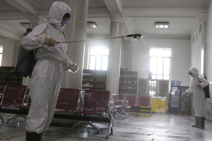 Women in protective suits disinfect a hall at the Pyongyang Railway Station to help curb the spread of the coronavirus in Pyongyang, North Korea, Thursday, Aug. 13, 2020. (AP Photo/Jon Chol Jin)