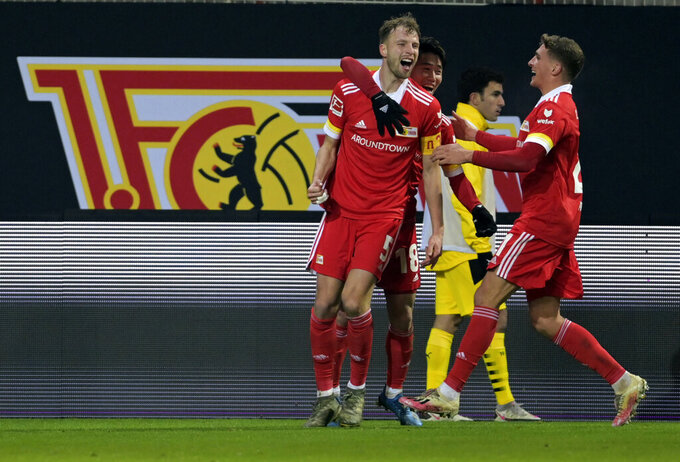 Union's Marvin Friedrich, left, celebrates after scoring his side's second goal of the game during the German Bundesliga soccer match between 1. FC Union Berlin and Borussia Dortmund at the Stadion Alte Forsterei in Berlin, Friday, Dec. 18, 2020. (Soeren Stache/Pool Photo via AP)