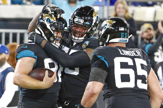 Jacksonville Jaguars offensive tackle Jawaan Taylor, center, and center Brandon Linder (65) celebrate with tight end Nick O'Leary, left, after O'Leary caught a 12-yard touchdown pass against the Los Angeles Chargers during the second half of an NFL football game, Sunday, Dec. 8, 2019, in Jacksonville, Fla. (AP Photo/Stephen B. Morton)