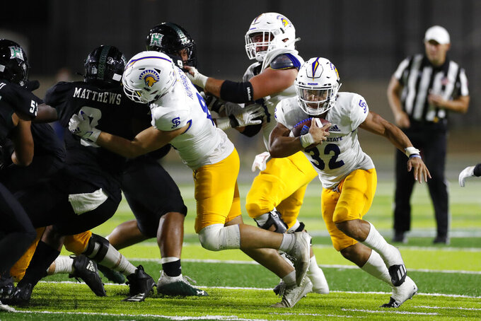 San Jose State running back Kairee Robinson (32) runs around the Hawaii defense during the second half of an NCAA college football game, Saturday, Sept. 18, 2021, in Honolulu. (AP Photo/Marco Garcia)