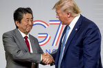 U.S President Donald Trump and Japanese Prime Minister Shinzo Abe, left, shake hands following a news conference at the G-7 summit in Biarritz, France, Sunday, Aug. 25, 2019, to announce that the U.S. and Japan have agreed in principle on a new trade agreement. (AP Photo/Andrew Harnik)