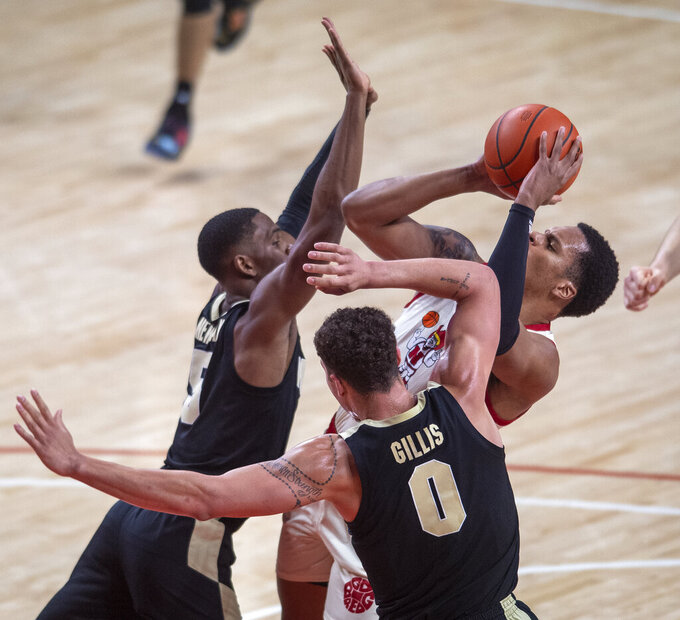 Nebraska guard Shamiel Stevenson, right, shoots under pressure from Purdue's Brandon Newman (5) and Mason Gillis (0) during the first half of an NCAA college basketball game on Saturday, Feb. 20, 2021, in Lincoln, Neb. (Francis Gardler/Lincoln Journal Star via AP)