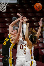 Iowa center Luka Garza (55) cannot get the rebound as Minnesota center Liam Robbins (0) and forward Brandon Johnson (23) also go for the ball during the first half of an NCAA college basketball game Friday, Dec. 25, 2020, in Minneapolis. (AP Photo/Bruce Kluckhohn)
