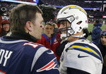 New England Patriots quarterback Tom Brady, left, and Los Angeles Chargers quarterback Philip Rivers speak at midfield after an NFL divisional playoff football game, Sunday, Jan. 13, 2019, in Foxborough, Mass. (AP Photo/Steven Senne)