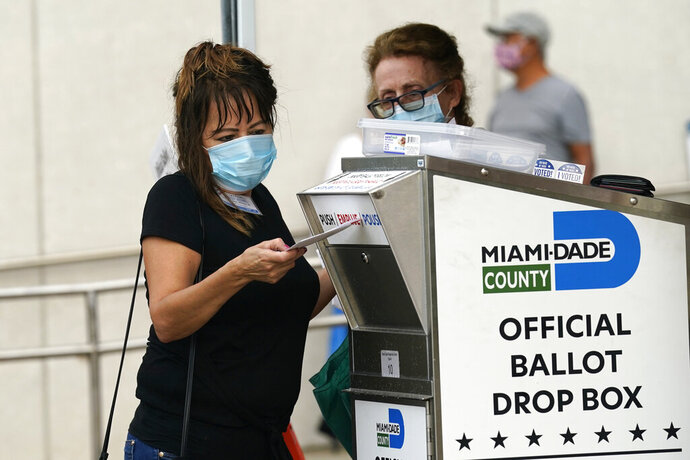 FILE - In this Monday, Oct. 19, 2020, file photo, an election worker places a vote-by-mail ballot into an official ballot drop box outside of an early voting site, in Miami. Just days before the presidential election, millions of mail-in ballots have still not been returned in key battleground states. Many of those are due in county offices by Tuesday, Nov. 3, but the latest Postal Service delivery data suggests it's too late for voters to drop their ballots in the mail. (AP Photo/Lynne Sladky, File)