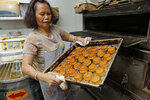 In this Friday, Aug. 9, 2019 photo, a staff member holds a tray of mooncakes with Chinese words