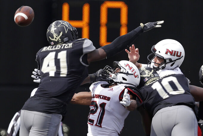 Northern Illinois quarterback Ross Bowers, right, gets rid of the ball as he is hit by Vanderbilt defensive lineman Dayo Odeyingbo (10) in the second half of an NCAA college football game Saturday, Sept. 28, 2019, in Nashville, Tenn. Vanderbilt won 24-18. (AP Photo/Mark Humphrey)