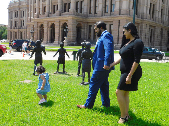 Donovon Rodriguez, chief of staff for Texas state Rep. Ray Lopez, walks around the Texas Capitol with his wife, Jenny Tavarez, and daughter, Evelyn Belle Rodriguez, for whom he is the sole provider, Monday, July 26, 2021, in Austin, Texas. Rodriguez could lose his job by Sept. 1, if legislative budget funding is not restored. (AP Photo/Acacia Coronado)