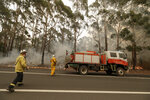 A firefighting crew battles a fire near Burrill Lake, Australia, Sunday, Jan. 5, 2020. Milder temperatures Sunday brought hope of a respite from wildfires that have ravaged three Australian states, destroying almost 2,000 homes. (AP Photo/Rick Rycroft)