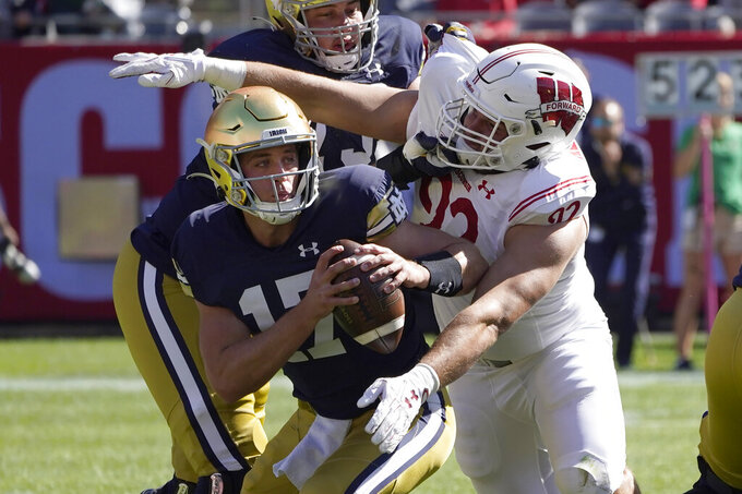 FILE - Wisconsin defensive end Matt Henningsen sacks Notre Dame quarterback Jack Coan during the first half of an NCAA college football game in Chicago, in this Saturday, Sept. 25, 2021, file photo. No team in the country runs the ball a greater percentage of the time than Army. No team does a better job of stopping the run than Wisconsin. That sets up an intriguing matchup Saturday night, Oct. 16. (AP Photo/Charles Rex Arbogast, File)