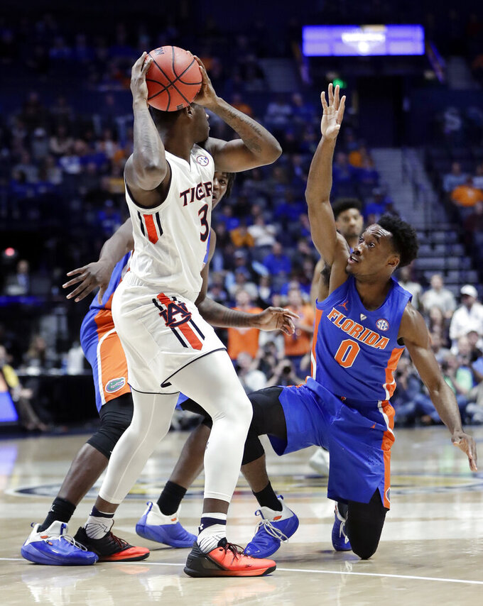 Florida guard Mike Okauru (0) stumbles as he defends against Auburn forward Danjel Purifoy (3) in the first half of an NCAA college basketball game at the Southeastern Conference tournament Saturday, March 16, 2019, in Nashville, Tenn. (AP Photo/Mark Humphrey)