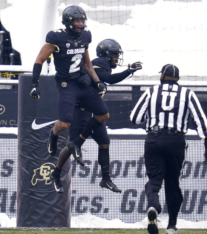 Colorado wide receiver Brenden Rice, left, celebrates catching a pass for a touchdown with wide receiver K.D. Nixon during the second half of an NCAA college football game against Utah, Saturday, Dec. 12, 2020, in Boulder, Colo. Utah won 38-21. (AP Photo/David Zalubowski)