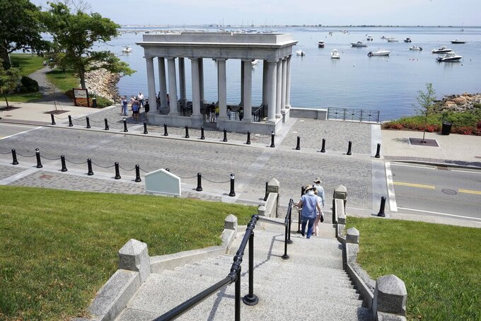 Pedestrians walk down stairs from Cole's Hill toward a pavilion that shelters Plymouth Rock, in Plymouth, Mass., Wednesday, June 9, 2021. Archaeologists are excavating the grassy hilltop that overlooks iconic Plymouth Rock one last time before a historical park is built on the site. (AP Photo/Steven Senne)
