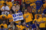 Fans hold up signs for injured Golden State Warriors forward Kevin Durant during the first half of Game 6 of basketball's NBA Finals between the Warriors and the Toronto Raptors in Oakland, Calif., Thursday, June 13, 2019. (AP Photo/Tony Avelar)