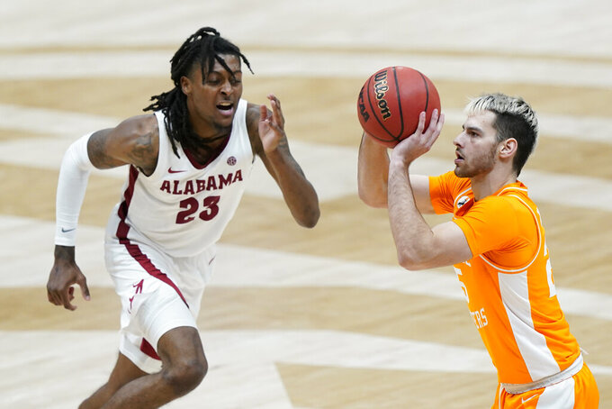 Tennessee's Santiago Vescovi, right, shoots as Alabama's John Petty Jr. (23) pressures him in the second half of an NCAA college basketball game in the Southeastern Conference Tournament Saturday, March 13, 2021, in Nashville, Tenn. (AP Photo/Mark Humphrey)