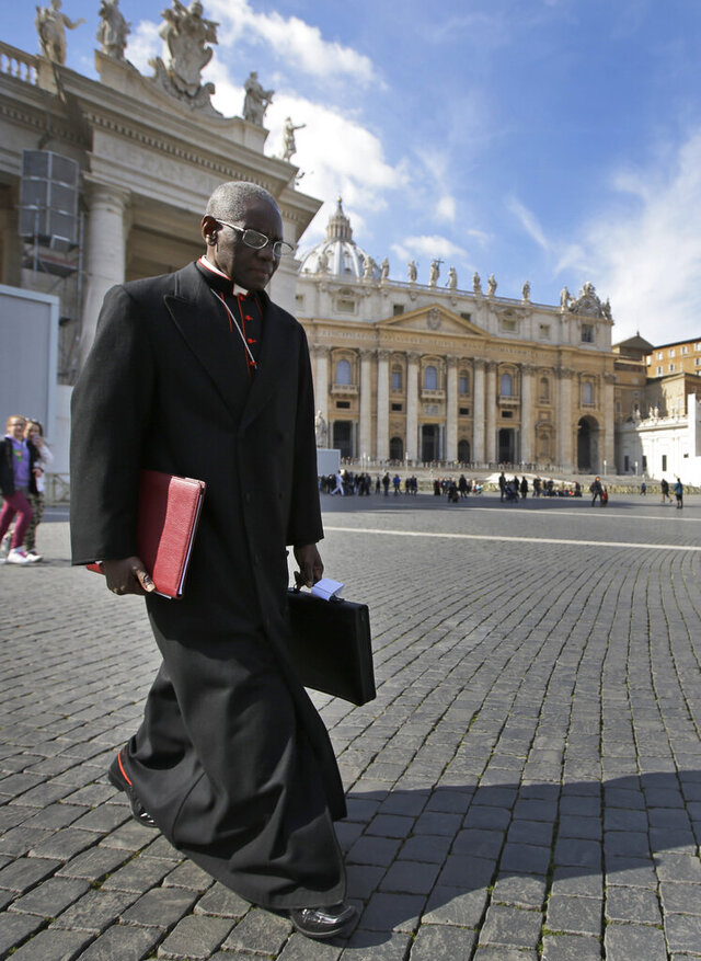 FILE - In this Monday, March 4, 2013 file photo, Cardinal Robert Sarah, of Guinea, walks in St. Peter's Square after attending a cardinals' meeting, at the Vatican. Retired Pope Benedict XVI wrote the book,