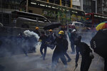Protesters face police tear smoke in Hong Kong, Sunday, Oct. 20, 2019. Hong Kong protesters again flooded streets on Sunday, ignoring a police ban on the rally and demanding the government meet their demands for accountability and political rights. (AP Photo/Felipe Dana)