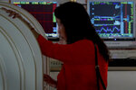 A woman checks stock prices at a brokerage house in Beijing, Thursday, Sept. 19, 2019. Shares were mixed in Asia on Thursday, with Tokyo and Sydney logging modest gains after the Federal Reserve cut its benchmark interest rate for a second time this year, citing slowing global economic growth and uncertainty over U.S. trade conflicts. (AP Photo/Andy Wong)