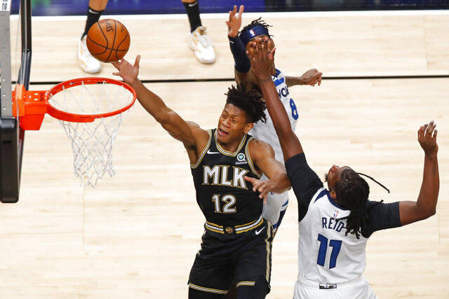 Atlanta Hawks forward De'Andre Hunter (12) goes up for a shot as center Naz Reid (11) and Minnesota Timberwolves forward Jarred Vanderbilt (8) defend in the first half of an NBA basketball game on Monday, Jan. 18, 2021, in Atlanta. (AP Photo/Todd Kirkland)