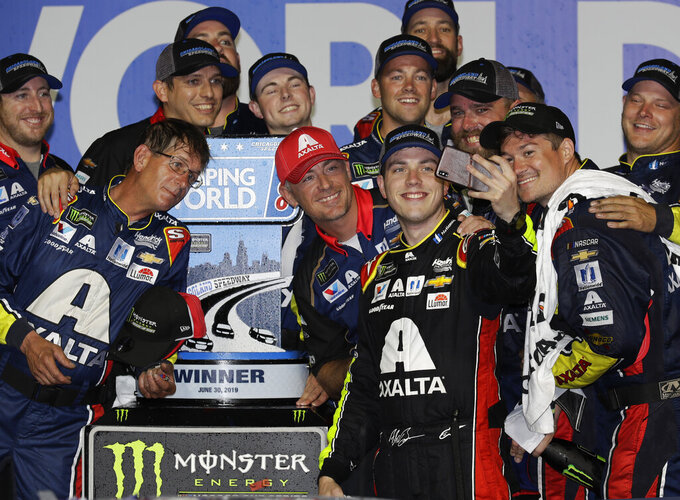 Alex Bowman takes photos of him and his crew after winning the NASCAR Cup Series auto race at Chicagoland Speedway in Joliet, Ill., Sunday, June 30, 2019. (AP Photo/Nam Y. Huh)