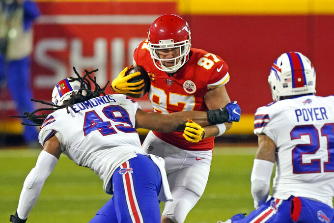 Kansas City Chiefs tight end Travis Kelce (87) runs from Buffalo Bills linebacker Tremaine Edmunds (49) and safety Jordan Poyer (21) after catching a pass during the first half of the AFC championship NFL football game, Sunday, Jan. 24, 2021, in Kansas City, Mo. (AP Photo/Charlie Riedel)