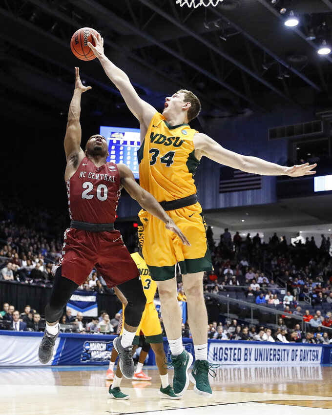 North Dakota State's Rocky Kreuser (34) blocks a shot by North Carolina Central's Julian Walters (20) during the first half of a First Four game of the NCAA men's college basketball tournament Wednesday, March 20, 2019, in Dayton, Ohio. (AP Photo/John Minchillo)
