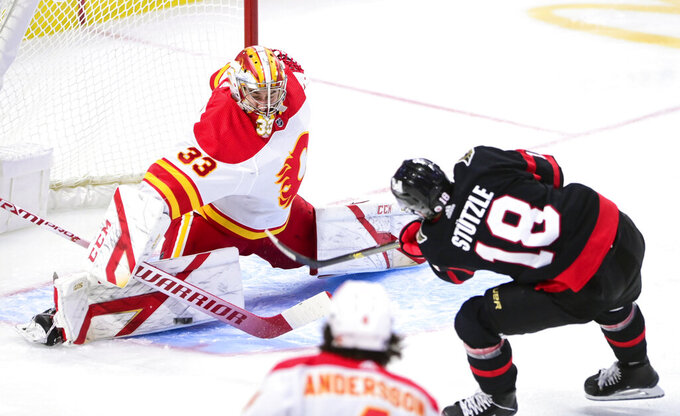 Calgary Flames goaltender David Rittich (33) makes a save on a shot from Ottawa Senators left wing Tim Stutzle (18) during second period NHL hockey action in Ottawa on Saturday, Feb. 27, 2021. (Sean Kilpatrick/The Canadian Press via AP)