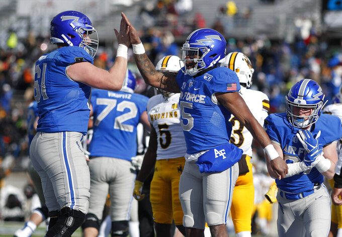 Air Force offensive lineman Scott Hattok, left, congratulates quarterback Donald Hammond III after his touchdown plunge against Wyoming in the first half of an NCAA college football game Saturday, Nov. 30, 2019, at Air Force Academy, Colo. (AP Photo/David Zalubowski)