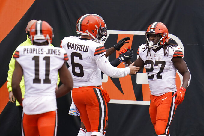 Cleveland Browns' Kareem Hunt (27) celebrates a touchdown with quarterback Baker Mayfield (6) during the second half of an NFL football game against the Cincinnati Bengals, Sunday, Oct. 25, 2020, in Cincinnati. (AP Photo/Michael Conroy)