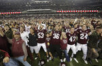 Fans and students join Texas A&M football players on the field after an NCAA college football game against LSU Saturday, Nov. 24, 2018, in College Station, Texas. Texas A&M won 74-72 in seven overtimes.(AP Photo/David J. Phillip)
