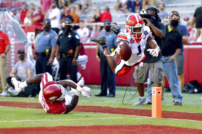 Georgia receiver George Pickens (1) dives into the end zone past Arkansas defender Jerry Jacobs (0) to score a touchdown during the second half of an NCAA college football game in Fayetteville, Ark., Saturday, Sept. 26, 2020. (AP Photo/Michael Woods)