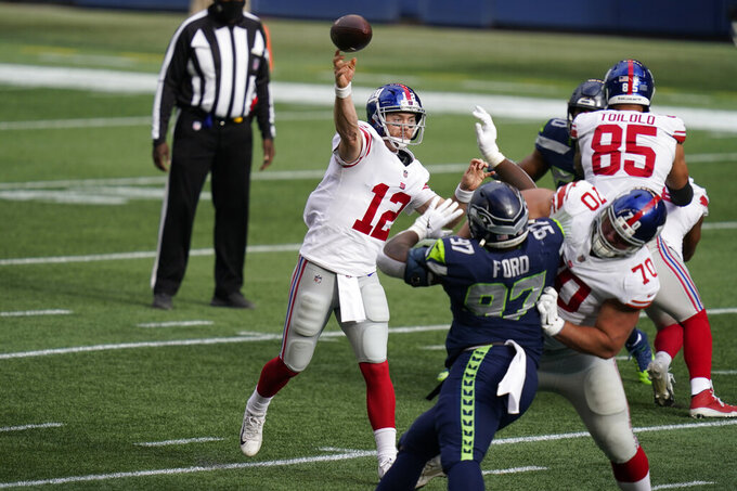 New York Giants quarterback Colt McCoy (12) passes as offensive guard Kevin Zeitler (70) blocks Seattle Seahawks defensive tackle Poona Ford (97) during the first half of an NFL football game, Sunday, Dec. 6, 2020, in Seattle. (AP Photo/Elaine Thompson)