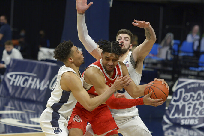 In the final minute of play, Ohio State's Justice Sueing, center, takes an inbound pass and is pressured by Penn State's Myreon Jones, eft, and Trent Buttrick, right, during the second half of an NCAA college basketball game, Thursday, Feb. 18, 2021, in State College, Pa. (AP Photo/Gary M. Baranec)