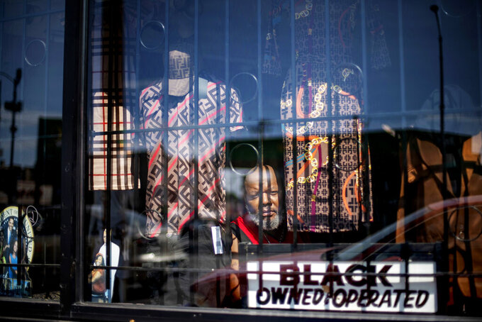 """Ronald Cashaw looks out from the window of his clothing store, Just Kicking, in the Auburn Gresham neighborhood of Chicago, Saturday, Aug. 22, 2020. Blocked by security bars, looters smashed the front window of his store grabbed some clothing and ran away before Cashaw arrived. """"I had tears in my eyes,"""" says Cashaw. The looting was something new, and horrible. But in the nearly two decades Cashaw has served this community, financial problems have grown more devastating. (AP Photo/David Goldman)"""