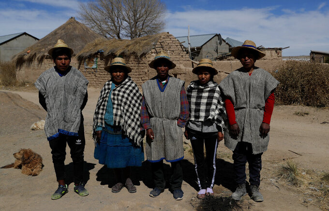 """Members of the Choque family, from left, Jose, Evarista Flores, Rufino, Abelina and Abdon, pose for a photo in the Urus del Lago Poopo indigenous community, in Punaca, Bolivia, Sunday, May 23, 2021. With no land for farming, the young men hire themselves out as laborers, herders or miners in nearby towns or more distant cities. """"They see the money and they don't return,"""" said Abdon.  (AP Photo/Juan Karita)"""