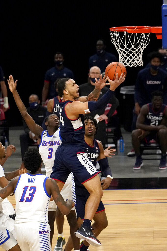 Connecticut's Tyrese Martin (4) drives to the basket between DePaul's Kobe Elvis (3) and Darious Hall during the second half of an NCAA college basketball game Monday, Jan. 11, 2021, in Chicago. (AP Photo/Charles Rex Arbogast)