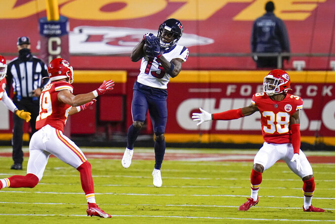 Houston Texans wide receiver Brandin Cooks (13) catches a pass between Kansas City Chiefs defenders Daniel Sorensen (49) and L'Jarius Sneed (38) in the first half of an NFL football game Thursday, Sept. 10, 2020, in Kansas City, Mo. (AP Photo/Jeff Roberson)