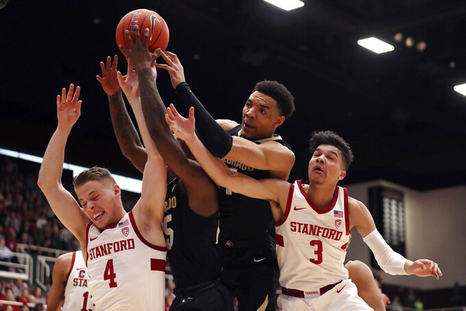 Colorado forward Tyler Bey (1) battles for a rebound against Stanford's Isaac White (4) and forward Tyrell Terry (3) during the first half of an NCAA college basketball game in Stanford, Calif., Sunday, March 1, 2020. (AP Photo/Jed Jacobsohn)