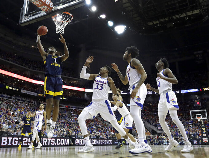 West Virginia's Derek Culver (1) gets past Kansas' David McCormack (33) to put up a shot during the first half of an NCAA college basketball game in the Big 12 men's tournament Friday, March 15, 2019, in Kansas City, Mo. (AP Photo/Charlie Riedel)