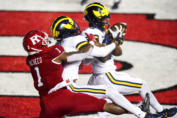 Michigan's Daxton Hill, right, intercepts a pass intended for Rutgers' Isaih Pacheco, left, as Michigan's Vincent Gray, center, defends during the third overtime of an NCAA college football game early Sunday, Nov. 22, 2020, in Piscataway, N.J. Michigan won 48-42. (AP Photo/Frank Franklin II)