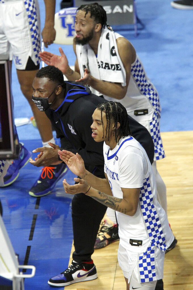 Kentucky's, from bottom up, B.J. Boston, Oscar Tshiebwe, and Davion Mintz, encourage their teammates from the sidelines late in the second half of an NCAA college basketball game in Lexington, Ky., Saturday, March 6, 2021. Kentucky won 92-64. (AP Photo/James Crisp)